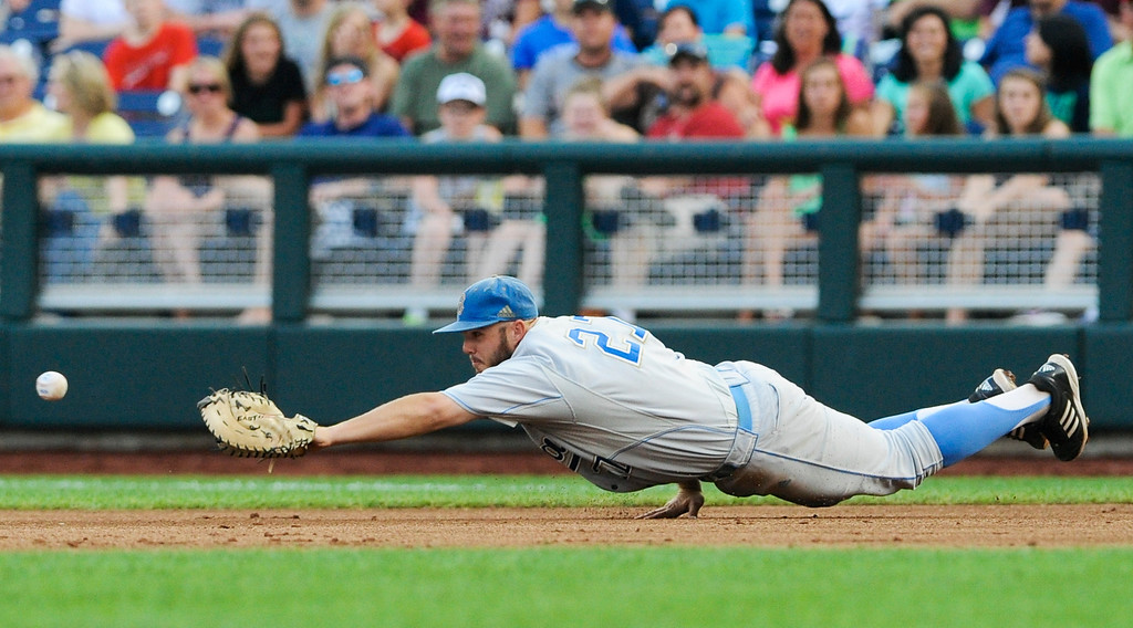 . UCLA first baseman Pat Gallagher stretches but cannot reach a ball hit for a single by Mississippi State\'s Brett Pirtle in the second inning of Game 1 of the NCAA College World Series best-of-three finals, in Omaha, Neb., Monday, June 24, 2013. (AP Photo/Eric Francis)