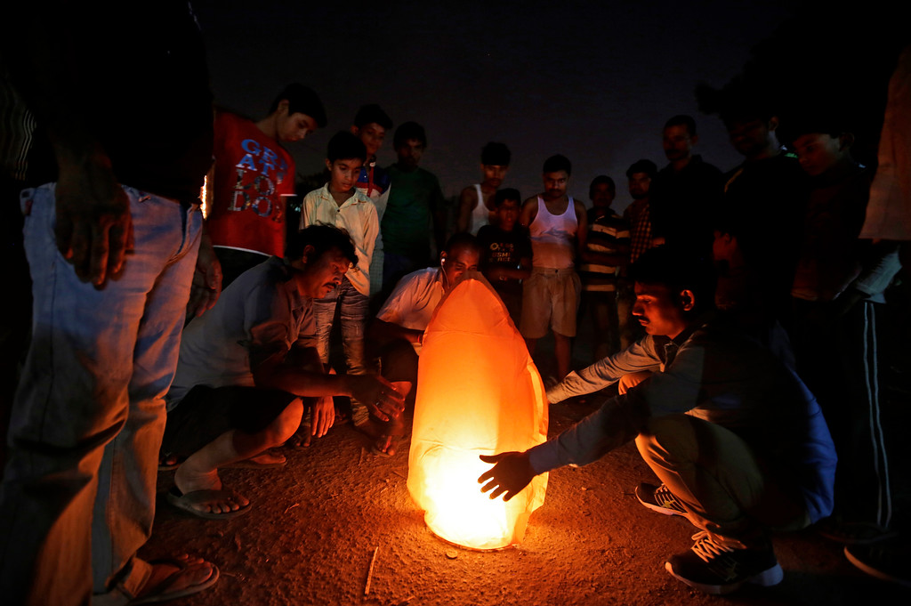 . Indians surround a sky lantern as they wait for it to take flight during Diwali festival in New Delhi, India, Thursday, Oct. 19, 2017. The Supreme Court this year banned the sale of firecrackers in the Indian capital and neighboring areas to prevent a toxic haze after the Diwali nights that has residents hiding indoors. (AP Photo/Altaf Qadri)