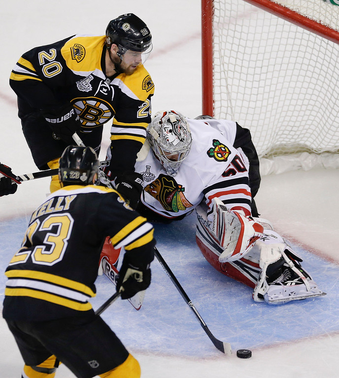 . Boston Bruins left wing Daniel Paille (20) moves the puck in front of Chicago Blackhawks goalie Corey Crawford (50) during the third period in Game 6 of the NHL hockey Stanley Cup Finals, Monday, June 24, 2013, in Boston. (AP Photo/Charles Krupa)