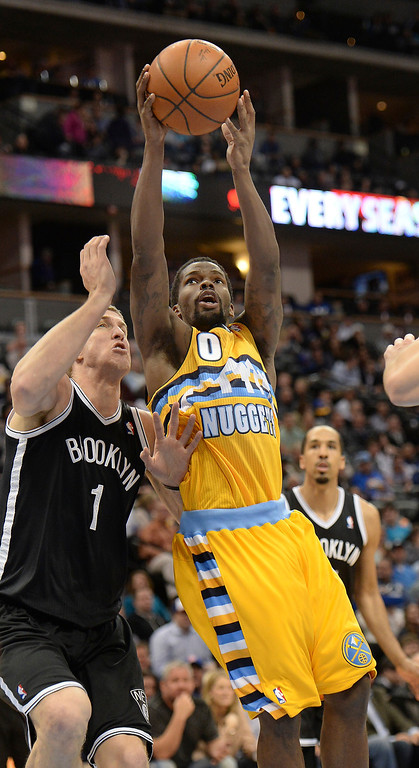 . DENVER, CO. - FEBRUARY 27, 2014: Denver guard Aaron Brooks (0) flew past Brooklyn defender Mason Plumlee (1) in the first half. The Denver Nuggets hosted the Brooklyn Nets at the Pepsi Center Thursday night, February 27, 2014. Photo By Karl Gehring/The Denver Post