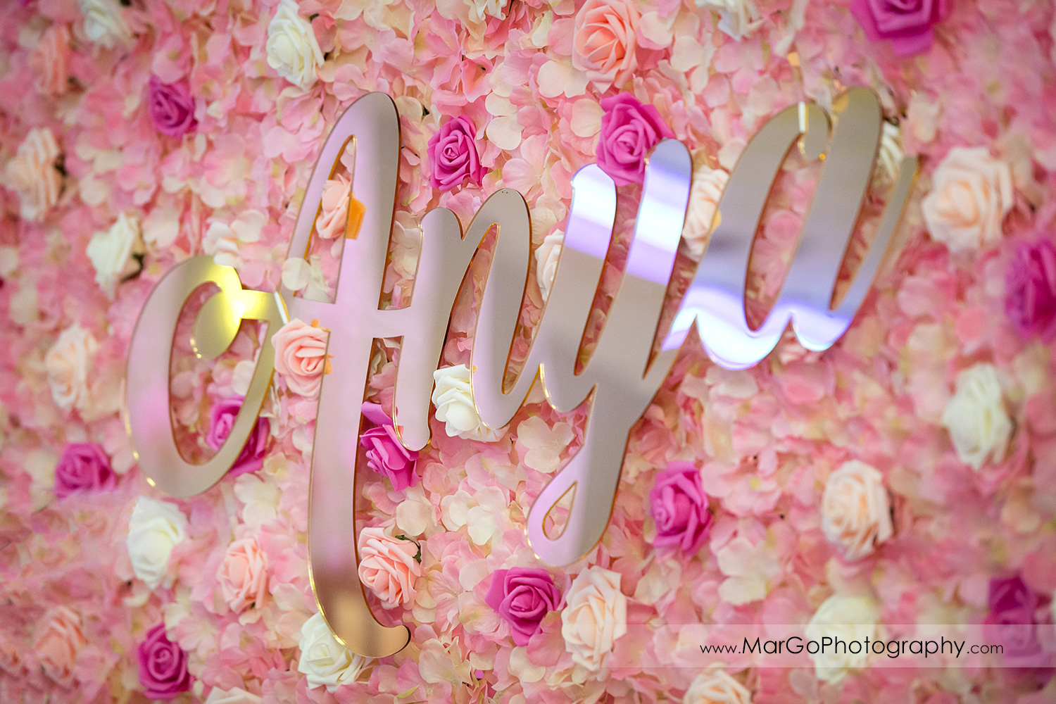 mirror sign on white and pink flower wall at Newark Oasis Palace