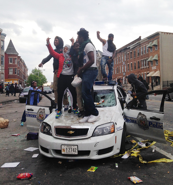 . EDS NOTE: OBSCENE GESTURES - People stand on top of a Baltimore police car in Baltimore on Monday, April 27, 2015, during unrest following the funeral of Freddie Gray. Gray died from spinal injuries about a week after he was arrested and transported in a Baltimore Police Department van. (AP Photo/Juliet Linderman)