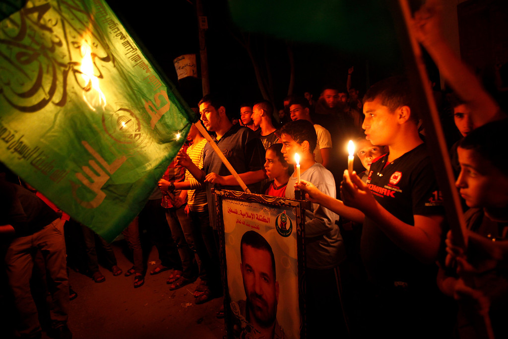 . Palestinian Hamas supporters hold candles as one waves a green Islamic flag at the site where Hamas\' military commander Ahmad Jabari was killed a year ago in an Israeli air strike during their battle, as they commemorate the anniversary of his death and the battle in Gaza City, Thursday, Nov. 14, 2013. (AP Photo/Adel Hana)