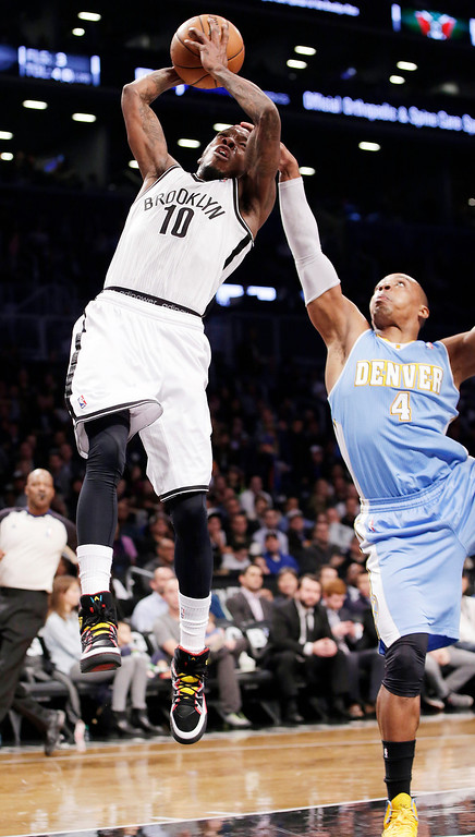 . Denver Nuggets guard Randy Foye (4) fouls Brooklyn Nets guard Tyshawn Taylor (10) in the first half of an NBA basketball game Tuesday, Dec. 3, 2013, in New York. (AP Photo/Kathy Willens)
