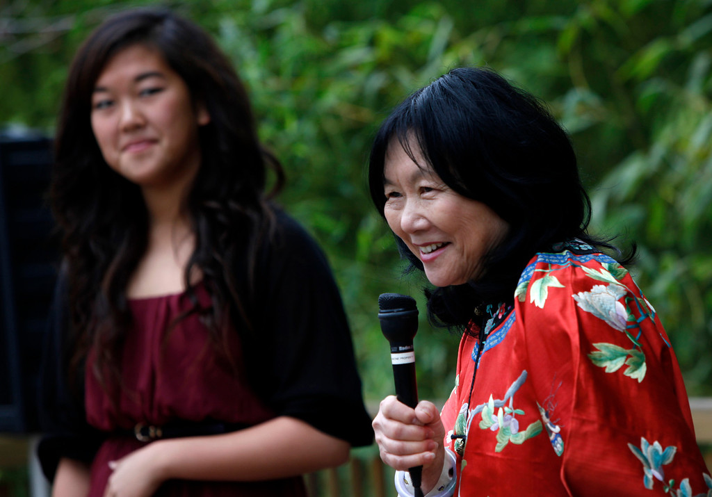 """. Connie Young Yu, the president of the nearly century-old Hakone Estate and Gardens, introduces zitherist Jennifer Liu at the Lunar New Year of the Snake festival and \""""Chinese Village Fair\"""" on Sunday afternoon, March 3, 2013 in Saratoga, Calif. (Karl Mondon/Staff)"""