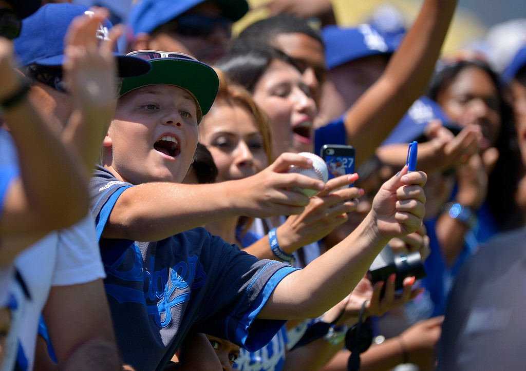 . Fans wait for members of the Los Angeles Dodgers during On-Field Photo Day before a baseball game against the Colorado Rockies, Saturday, July 13, 2013, in Los Angeles. (AP Photo/Mark J. Terrill)
