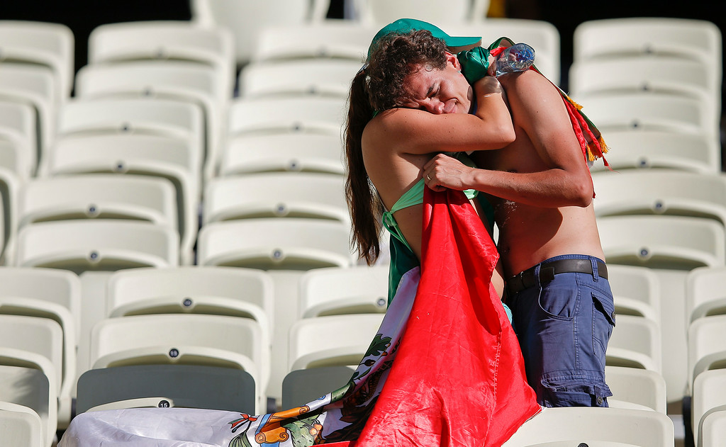 . Mexican supporters hug in the stand after the Netherlands defeated Mexico 2-1 to advance to the quarterfinals during the World Cup round of 16 soccer match between the Netherlands and Mexico at the Arena Castelao in Fortaleza, Brazil, Sunday, June 29, 2014. (AP Photo/Eduardo Verdugo)