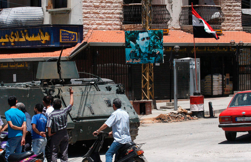 . A picture of Syria\'s President Bashar al-Assad and a Syrian national flag are seen on a street as Lebanese army soldiers patrol the Alawite Jabal Mohsen neighborhood, after being deployed to tighten security following clashes between Sunni Muslims and Alawites, in the port city of Tripoli, northern Lebanon June 5, 2013. Twenty nine people were killed last month in the deadliest fighting yet between gunmen sympathetic to the uprising against Bashar al-Assad and Alawite supporters of the Syrian president. REUTERS/Stringer