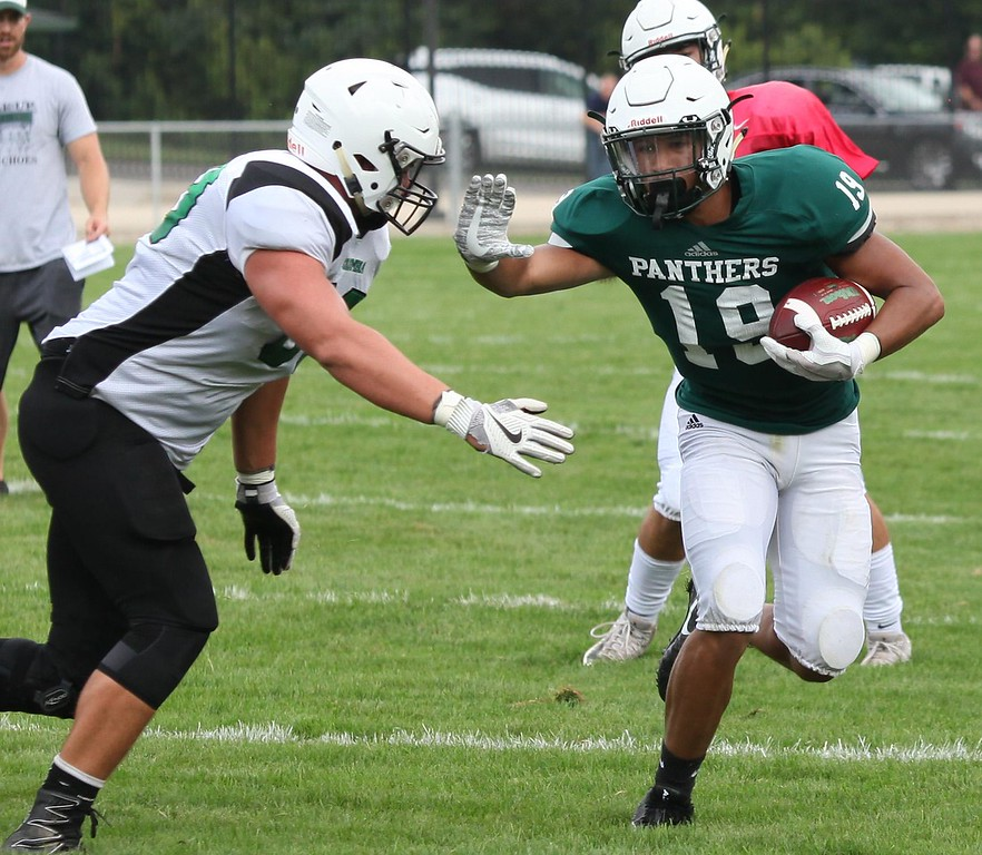 . Randy Meyers - The Morning Journal Nick Bender of Elyria Catholic stiff-arms a Columbia defender after a short gain during a scrimmage.