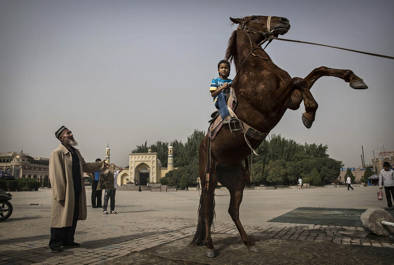 . KASHGAR, CHINA - JULY 28:  A Uyghur boy sits atop a horse as he has his picture taken outside the Id Kah Mosque before the Eid holiday  on July 28, 2014 in old Kashgar, Xinjiang Province, China. Nearly 100 people have been killed in unrest in the restive Xinjiang Province in the last week in what authorities say is terrorism but advocacy groups claim is a result of a government crackdown to silence opposition to its policies. China\'s Muslim Uyghur ethnic group faces cultural and religious restrictions by the Chinese government. Beijing says it is investing heavily in the Xinjiang region but Uyghurs are increasingly dissatisfied with the influx of Han Chinese and uneven economic development.  (Photo by Kevin Frayer/Getty Images)