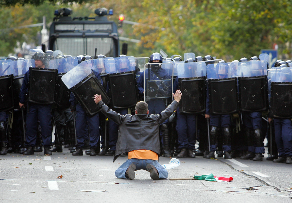 . A protestor faces a line of riot police during an anti-government protest in Budapest  October 23, 2006. Police fired rubber bullets to try to disperse anti-government protesters marching towards parliament on the 50th anniversary of Hungary\'s uprising against Soviet rule, a witnesses said.  REUTERS/Laszlo Balogh