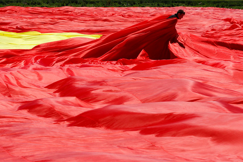. A worker arranges Romania\'s national flag during a Guinness World Record attempt for the world\'s biggest national flag in Clinceni, near Bucharest May 27, 2013.  The flag, measuring 349.4 per 226.9 meters, established a new Guinness World Record, according to the organization\'s officials. REUTERS/Bogdan Cristel