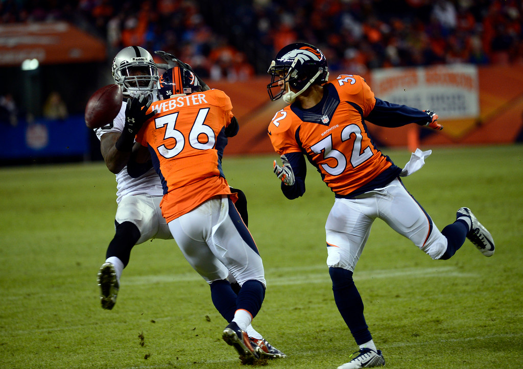 . DENVER, CO - DECEMBER 28: Kayvon Webster (36) of the Denver Broncos hits James Jones (89) of the Oakland Raiders breaking up the pass in the fourth quarter.  The Denver Broncos played the Oakland Raiders at Sports Authority Field at Mile High in Denver on December, 28 2014. (Photo by Tim Rasmussen/The Denver Post)