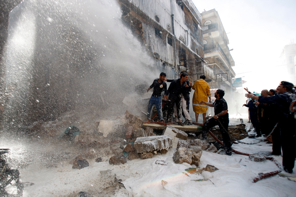 . Yemeni civilians and soldiers works to extinguish fire at the site of a plane crash in Sanaa, Yemen, Tuesday, Feb. 19, 2013. A Yemeni official says a military plane on a training exercise crashed into a neighborhood in the country\'s capital, Sanaa, killing and injuring scores of people. (AP Photo/Hani Mohammed)