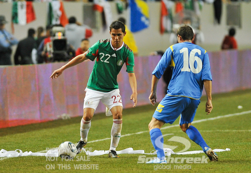 Mexico's Defender Paul Aguilar (#22) attempts to get around Bosnia-Herzegovina's Midfielder Senad Lulic (#16) during Soccer action between Bosnia-Herzegovina and Mexico.  Mexico defeated Bosnia-Herzegovina 2-0 in the game at the Georgia Dome in Atlanta, GA.