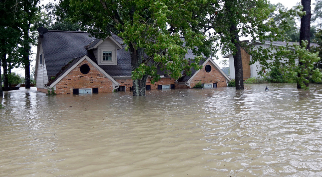 . A home is surrounded by floodwaters from Tropical Storm Harvey on Monday, Aug. 28, 2017, in Spring, Texas. Homeowners suffering from Harvey flood damage are more likely to be on the hook for losses than victims of prior storms, a potentially crushing blow to personal finances and neighborhoods along the Gulf Coast. Experts say far too few homeowners have flood insurance, just two of ten living in Harvey�s path of destruction. (AP Photo/David J. Phillip)