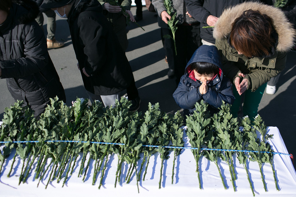 . People pray for victims of the tsunami on March 11, 2013 in Ootsuti, Iwate prefecture, Japan.  On March 11 Japan commemorates the second anniversary of the magnitude 9.0 earthquake and tsunami that claimed more than 18,000 lives.  (Photo by Ken Ishii/Getty Images)