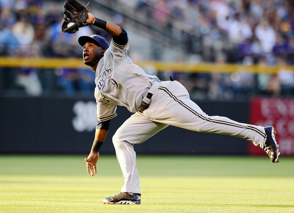 . Milwaukee Brewers shortstop Jean Segura makes a catch in the second inning of a baseball against the Colorado Rockies, Friday, July 26, 2013, in Denver. (AP Photo/Chris Schneider)