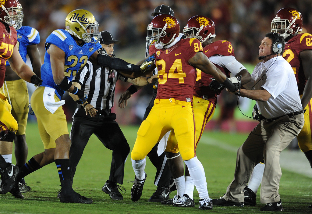 . UCLA Anthony Jefferson and USC Darreus Rogers get in a tussle while coach Ed Orgeron holds Rogers back in the first quarter. UCLA and USC played in a matchup of cross town rivals at the Los Angeles Memorial Coliseum in Los Angeles, CA.  photo by (John McCoy/Los Angeles Daily News)