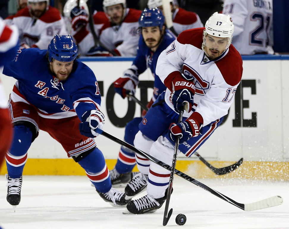 . New York Rangers right wing Derek Dorsett (15) defends Montreal Canadiens left wing Rene Bourque (17) during the third period of Game 4 of the NHL hockey Stanley Cup playoffs Eastern Conference finals, Sunday, May 25, 2014, in New York. (AP Photo/Kathy Willens)