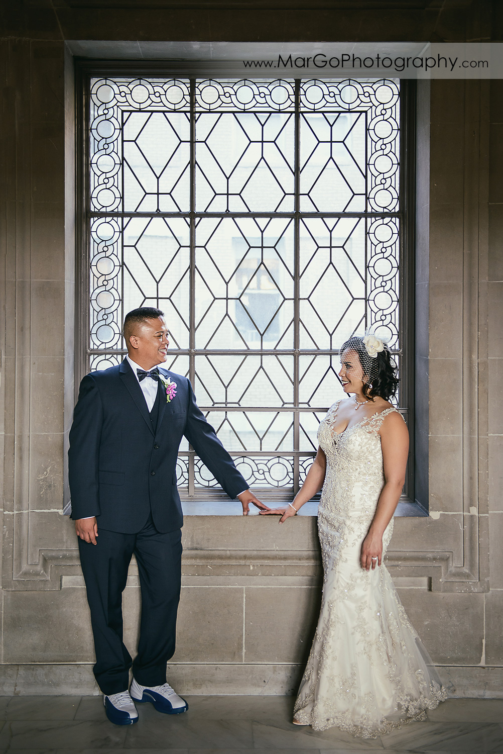 bride and groom in front of the stained glass window at San Francisco City Hall