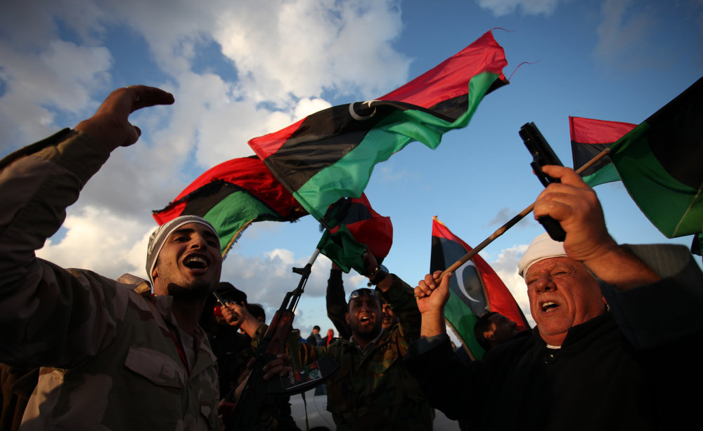Description of . Libyans wave national flags as they chant pro-revolutionary slogans during commemorations to mark the second anniversary of the revolution that ousted Moammar Gadhafi in Benghazi, Libya, Friday, Feb, 15, 2013. (AP Photo/Mohammad Hannon)