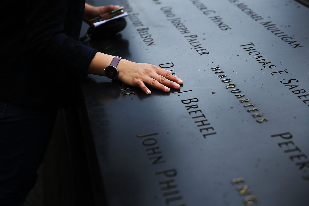 . A woman places a hand on the names engraved along the South reflecting pool at the Ground Zero memorial site during the dedication ceremony of the National September 11 Memorial Museum in New York on Thursday, May 15, 2014.  (AP Photo/Spencer Platt, Pool)