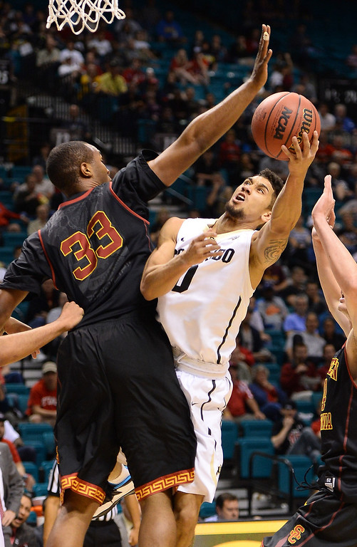 . Askia Booker #0 of the Colorado Buffaloes drives to the basket against D.J. Haley #33 of the USC Trojans of the USC Trojans during a first-round game of the Pac-12 Basketball Tournament at the MGM Grand Garden Arena on March 12, 2014 in Las Vegas, Nevada.  (Photo by Ethan Miller/Getty Images)