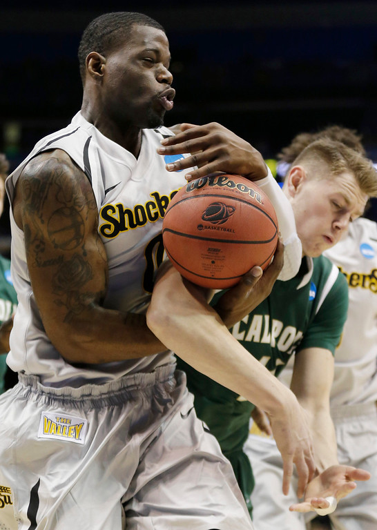 . Wichita State forward Chadrack Lufile (0) and Cal Poly forward Zach Gordon (44) go after a rebound during the first half of a second-round game in the NCAA college basketball tournament Friday, March 21, 2014, in St. Louis. (AP Photo/Charlie Riedel)