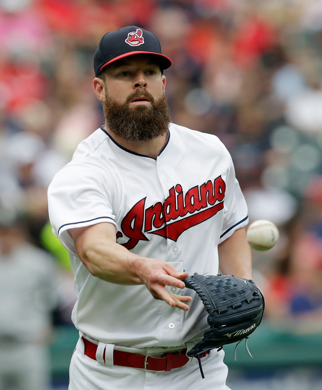 . Cleveland Indians starting pitcher Corey Kluber tosses the ball to get Chicago White Sox Jose Abreu out at first base in the fourth inning of a baseball game, Wednesday, June 20, 2018, in Cleveland. (AP Photo/Tony Dejak)