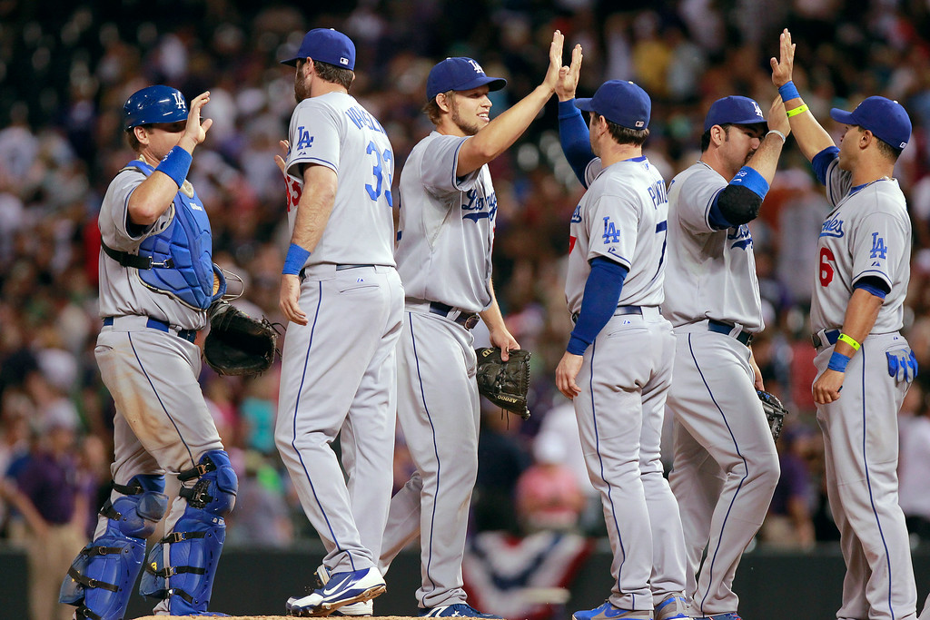 . Los Angeles Dodgers starting pitcher Clayton Kershaw, third from left, celebrates with teammates after pitching a four-hitter against the Colorado Rockies in a baseball game Tuesday, July 2, 2013, in Denver. The Dodgers won 8-0. (AP Photo/Barry Gutierrez)