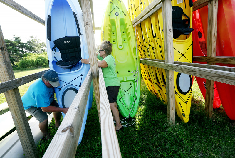 . Eddie Skakle and his wife Gail secure kayaks at their kayak rental business, A. S. Austin Co., in Hatteras Village, N.C., on Thursday, July 3, 2014. Hurricane Arthur is forecast to pass by North Carolina\'s Hatteras Island Friday morning. The island is under mandatory evacuation orders.  (AP Photo/The Virginian-Pilot, Steve Earley)