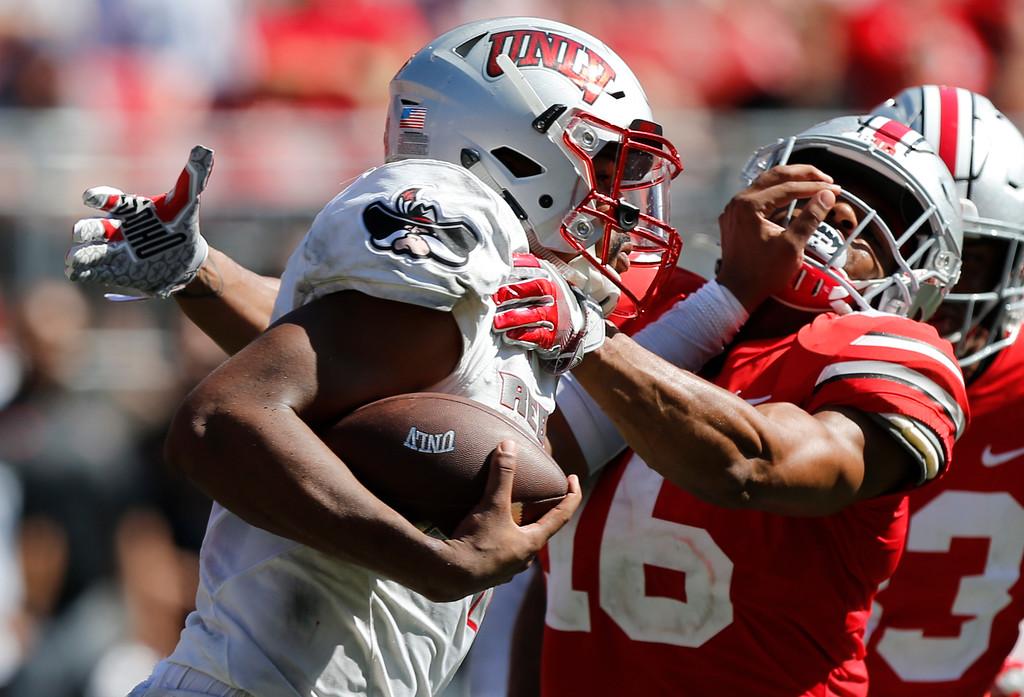 . UNLV quarterback Armani Rogers, left, stiff arms Ohio State linebacker Keandre Jones during the second half of an NCAA college football game Saturday, Sept. 23, 2017, in Columbus, Ohio. Ohio State beat UNLV 54-21. (AP Photo/Jay LaPrete)