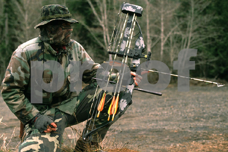 Bowhunter using a compound bow waits for a shot.