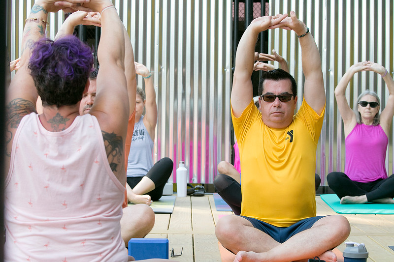 The first day of free outdoor yoga started Saturday at 9:30 AM at the new Mill Street stage, July 27, 2019. Instructor Cera Hawkins of Good Karma Yoga Therapy in Fitchburg leads the class. Following along during the class is Joe Bowen of Fitchburg, in Yellow.  SENTINEL & ENTERPRISE/JOHN LOVE
