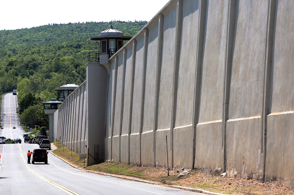 . Law enforcement officers stand guard near one of the walls of the Clinton Correctional Facility in Dannemora, N.Y. on Saturday, June 6, 2015. Two convicted murderers used power tools to cut through steel pipes at the maximum-security prison near the Canadian border and escaped through a manhole, Gov. Andrew Cuomo said Saturday. (Gabe Dickens/Press-Republican via AP)