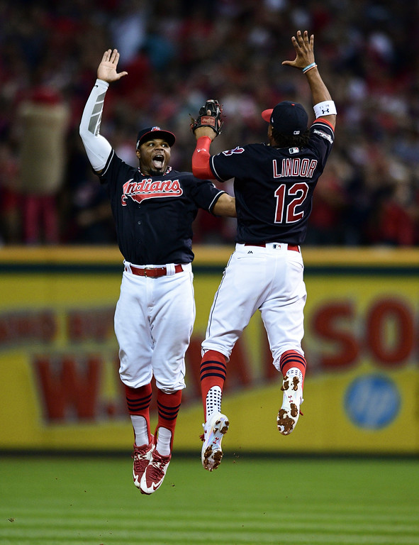 . Cleveland Indians outfielders Rajai Davis and Francisco Lindor (12) celebrate after defeating the Boston Red Sox in Game 2 of baseball\'s American League Division Series, Friday, Oct. 7, 2016, in Cleveland. (AP Photo/David Dermer) and