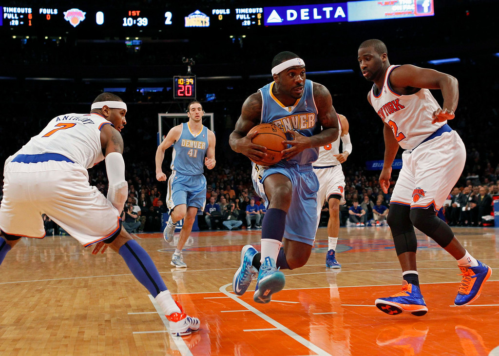 . Denver Nuggets point guard Ty Lawson drives to the basket between New York Knicks point guard Raymond Felton (R) and forward Carmelo Anthony in the first quarter of their NBA basketball game at Madison Square Garden in New York, December 9, 2012. REUTERS/Adam Hunger