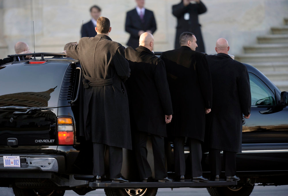 Description of . U.S. Secret Service agents ride on stepbar on the outside of their vehicle as they follow President Barack Obama as he leaves Capitol Hill in Washington, Monday, Jan. 21, 2013, following his ceremonial swearing-in ceremony during the 57th Presidential Inauguration. (AP Photo/Cliff Owen)