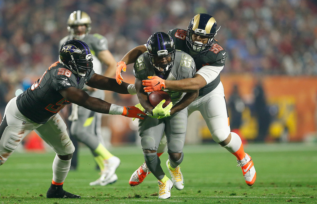 . GLENDALE, AZ - JANUARY 25: Team Carter running back Justin Forsett #29 of the Baltimore Ravens is grabbed by Team Irvin outside linebacker Elvis Dumervil #58 of the Baltimore Ravens (left) and defensive tackle Aaron Donald #99 of the St. Louis Rams (right) during the second half of the 2015 Pro Bowl at University of Phoenix Stadium on January 25, 2015 in Glendale, Arizona.  (Photo by Christian Petersen/Getty Images)