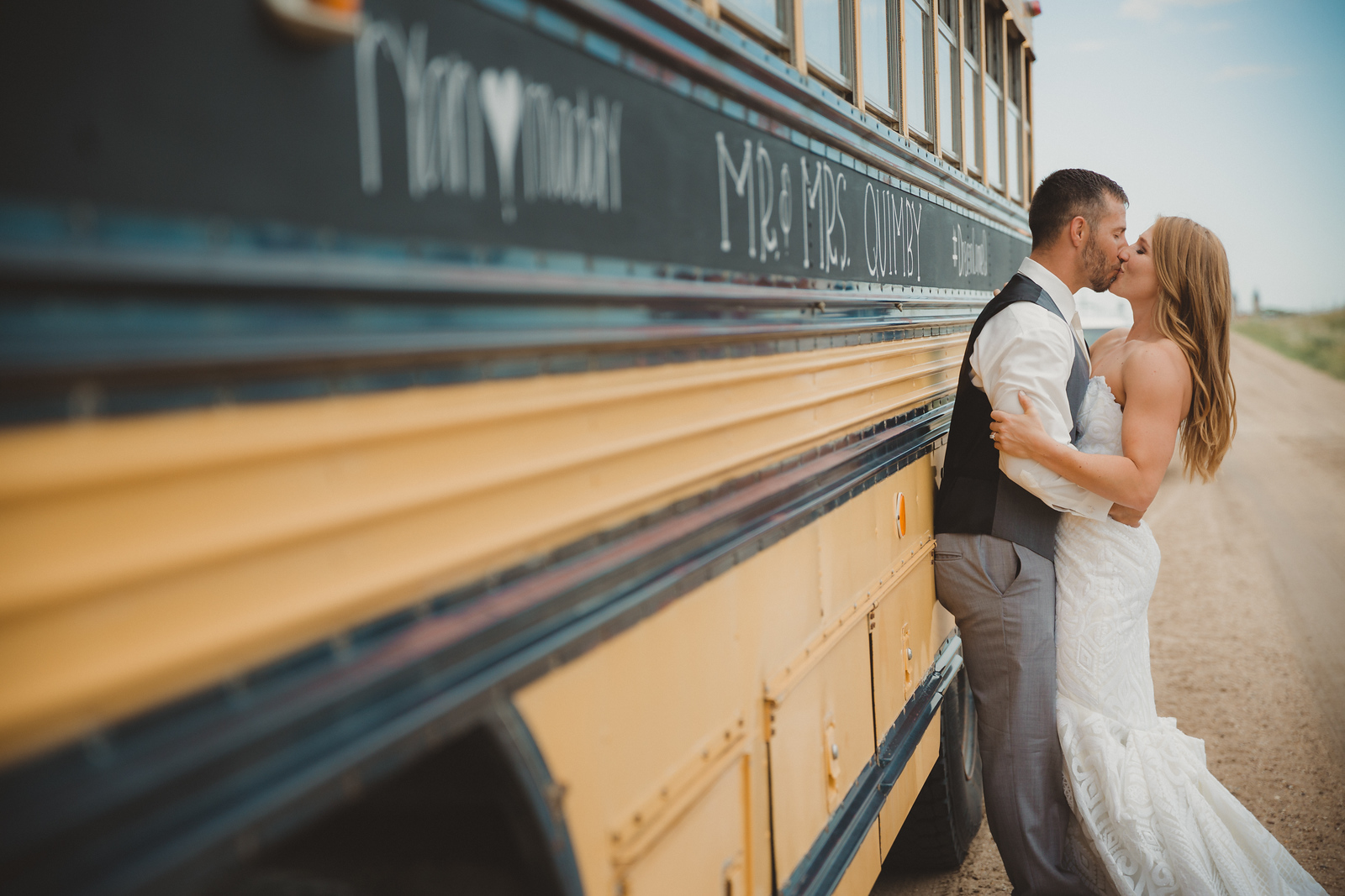 Newlywed P.E. Teachers share a kiss next to school bus