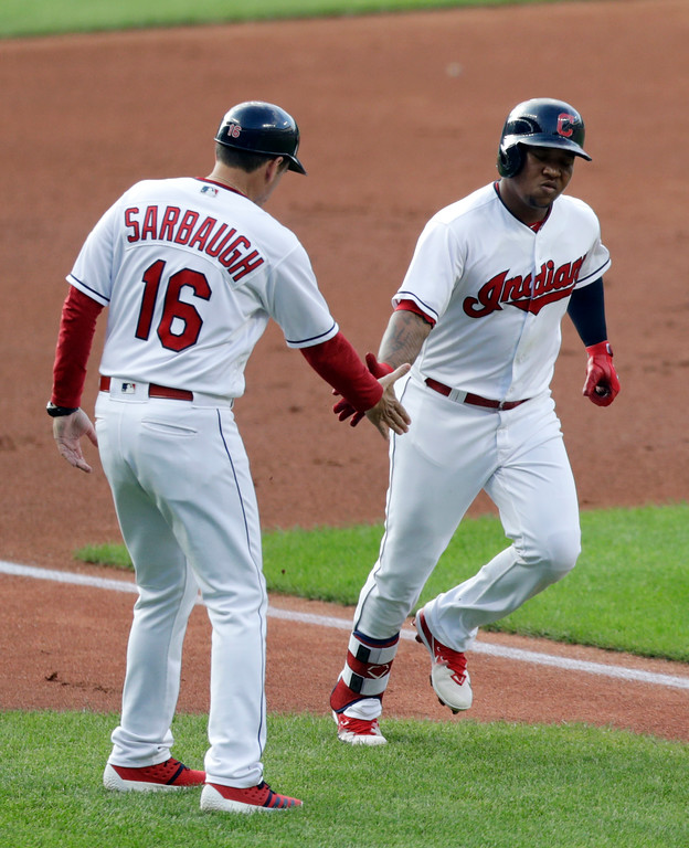 . Cleveland Indians\' Jose Ramirez, right, is congratulated by third base coach Mike Sarbaugh after Ramirez hit a solo home run off Cincinnati Reds starting pitcher Sal Romano during the first inning of a baseball game Tuesday, July 10, 2018, in Cleveland. (AP Photo/Tony Dejak)