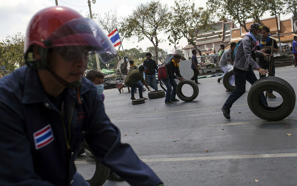 . Anti-government protesters roll tires down the street as they advance their position on retreating police at Phan Fah Bridge in Bangkok on February 18, 2014. AFP PHOTO / KC Ortiz/AFP/Getty Images