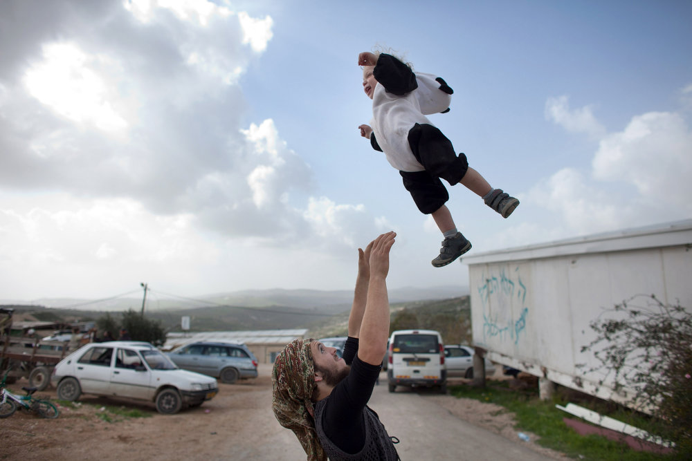 Description of . A Jewish settler plays with his baby as settlers celebrate the Jewish festival of Purim February 24, 2013 at the settlement outpost of Havat Gilad, West Bank. The carnival-like Purim holiday is celebrated with parades and costume parties to commemorate the deliverance of the Jewish people from a plot to exterminate them in the ancient Persian empire 2,500 years ago, as described in the Book of Esther. (Photo by Uriel Sinai/Getty Images)