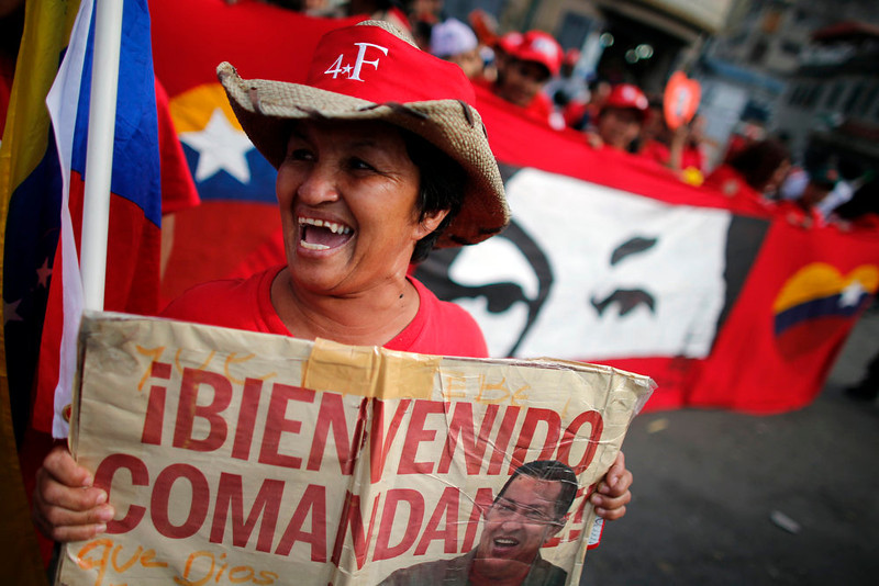 ". Supporters of Venezuela\'s President Hugo Chavez cheer outside the military hospital after his surprise return to Caracas February 18, 2013. Chavez made a surprise return from Cuba on Monday more than two months after surgery for cancer that has jeopardized his 14-year rule of the South American OPEC member. The 58-year-old socialist leader underwent a six-hour operation in Cuba on December 11, 2012. He had not been seen or heard in public since then until photos were published of him on Friday. The banner reads: ""Welcome commander\"". REUTERS/Jorge Silva"
