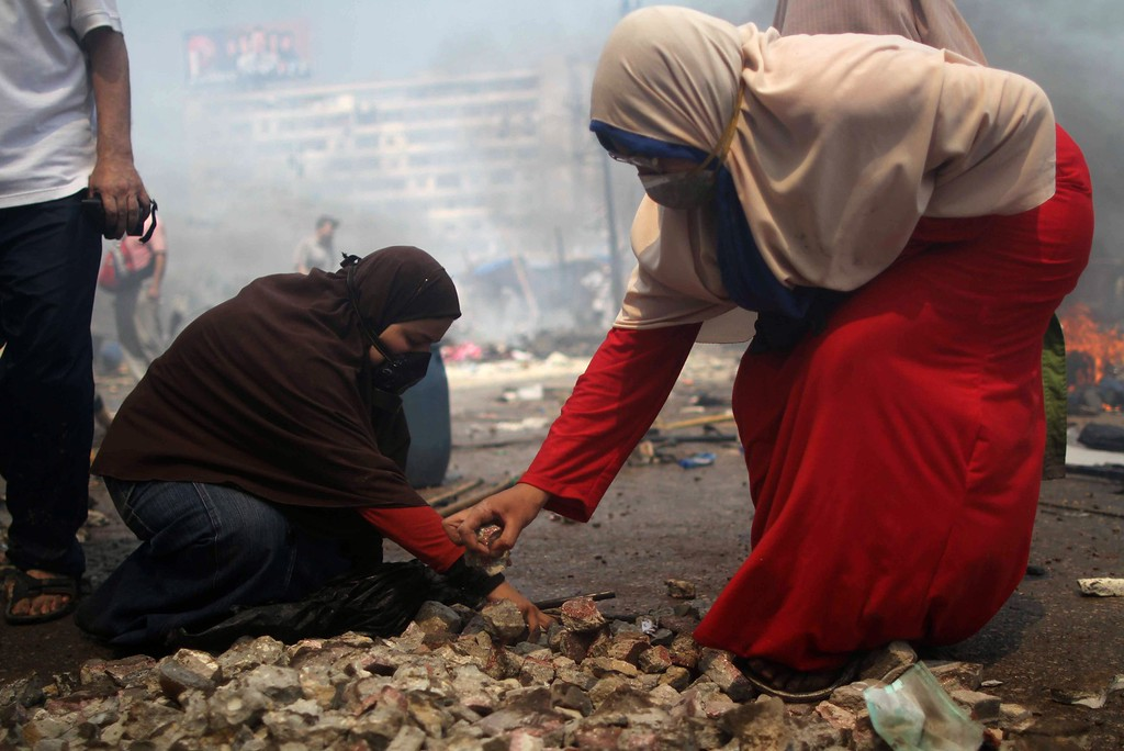 . A female supporters of the Muslim Brotherhood and Egypt\'s ousted president Mohamed Morsi gather stones during clashes with police in Cairo on August 14, 2013, as security forces backed by bulldozers moved in on two huge pro-Morsi protest camps, launching a long-threatened crackdown that left dozens dead.  AFP PHOTO / MOSAAB  EL-SHAMY/AFP/Getty Images