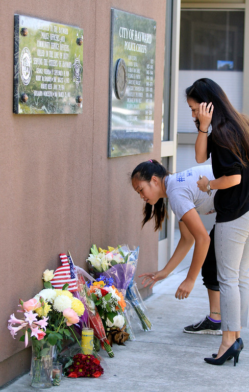 . Elaine Ma, right, and her sister Melissa Ma place flowers  outside the Hayward Police Department for Sgt. Scott Lunger in Hayward, Calif., on Wednesday, July 22, 2015. Lunger  was shot and killed early Wednesday morning during a routine traffic stop. The sisters\' father works for the Oakland Police Department and said this incident hits so close to home because Sgt. Lunger also has two daughters that he left behind. (Laura A. Oda/Bay Area News Group)