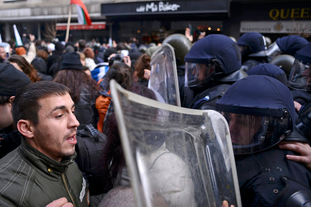 Description of . A man argues with a riot policeman during a protest against high electricity bills in Sofia February 17, 2013. Tens of thousands of Bulgarians protested in more than 20 cities against high electricity bills on Sunday, piling pressure on the government after a week of persistent demonstrations.  REUTERS/Tsvetelina Belutova