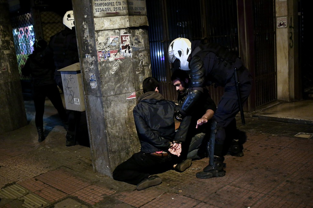 . Greek riot policemen arrest two protesters during clashes with demonstrators commemorating the six-year anniversary of the fatal shooting of teenager Alexis Grigoropoulos by a police officer, an event that plunged Greece into weeks of youth riots, in Athens on December 6, 2014.  AFP PHOTO/ANGELOS TZORTZINIS/AFP/Getty Images