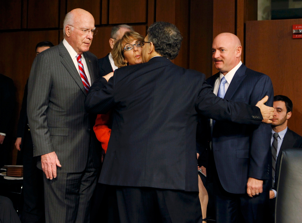 . Former U.S. Rep. Gabrielle Giffords (C) gets a kiss from U.S. Senator Al Franken (D-MN) as Senator Patrick Leahy (L) (D-VT) and her husband, retired astronaut and Navy Captain Mark Kelly (R) look on during a hearing held by the Senate Judiciary committee about guns and violence on Capitol Hill in Washington, January 30, 2013.  REUTERS/Larry Downing